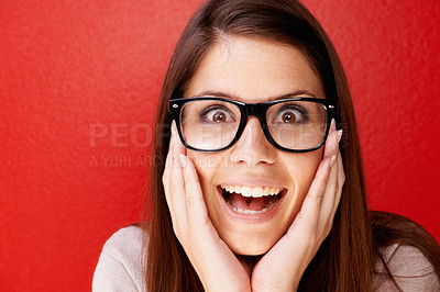 Buy stock photo Studio shot of a beautiful young woman wearing glasses against a red background