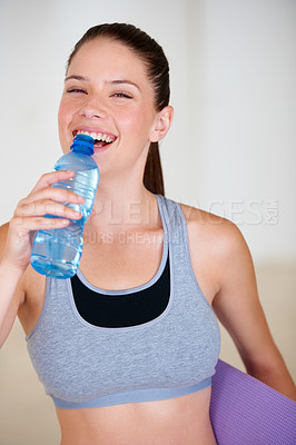 Buy stock photo Portrait of an attractive young woman drinking a bottle of water