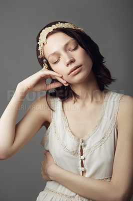 Buy stock photo A beautiful young woman wearing vintage clothing and posing with eyes closed and hand on her cheek