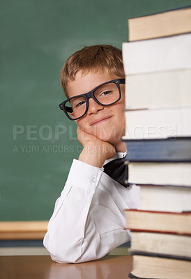 Buy stock photo A young boy wearing glasses and a bow-tie smiling at the camera from behind a stack of books