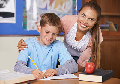 Buy stock photo A supportive young teacher leaning over her student while he writes in a book - portrait