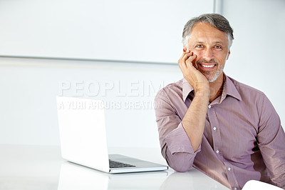 Buy stock photo Cropped shot of a young businessman sitting at his work desk