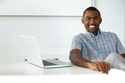 Buy stock photo A handsome ethnic businessman seated at a desk alongside a laptop