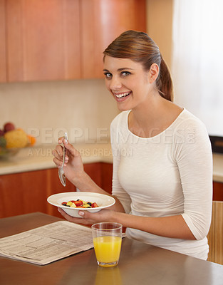 Buy stock photo Portrait of a beautiful young woman eating her breakfast in the kitchen