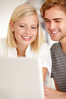 Buy stock photo A happy young couple using a laptop to surf the net