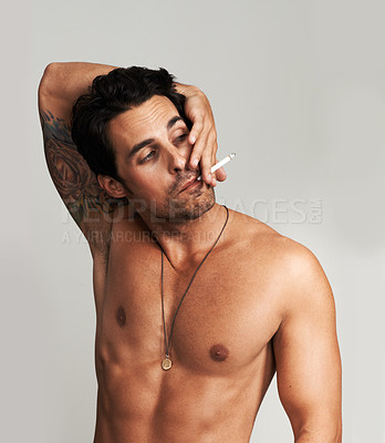 Buy stock photo A shirtless young man smoking a cigarette