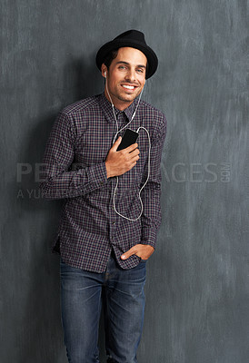 Buy stock photo Portrait of a hip young man listening to music on his mobile