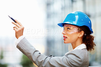 Buy stock photo Cute female architect pointing upwards with a pen