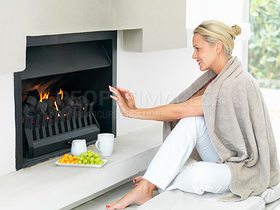 Buy stock photo Mature woman relaxing by a fireplace , warming herself at home