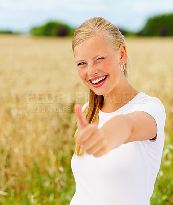 Buy stock photo Happy beautiful young woman showing thumbs up at a field