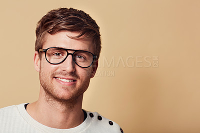 Buy stock photo Studio portrait of a handsome young man wearing glasses and smiling at the camera