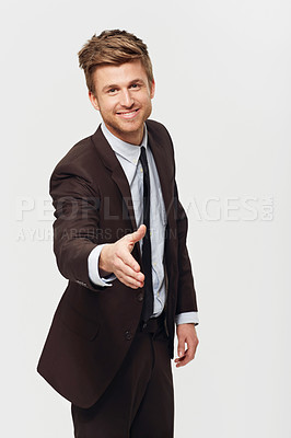 Buy stock photo Studio portrait of a stylishly-dressed young businessman giving a handshake toward the camera