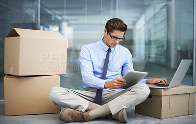 Buy stock photo A young businessman sitting on the floor working on a laptop and tablet while surrounded by boxes