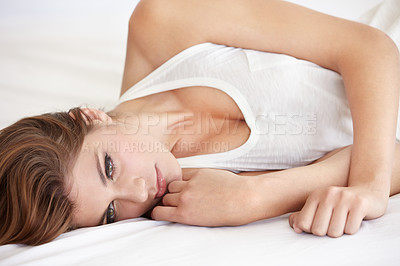 Buy stock photo A stunning young woman lying on her bed in a sleepshirt and looking away thoughtfully