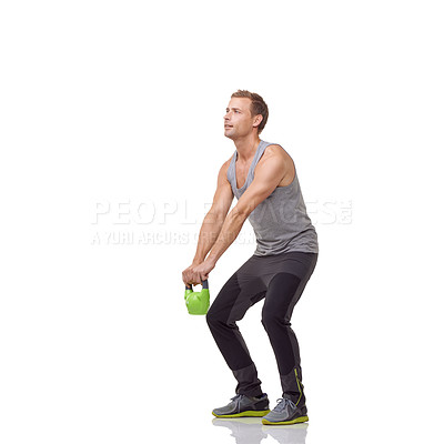 Buy stock photo A handsome young man working out with a kettle bell while isolated on a white background