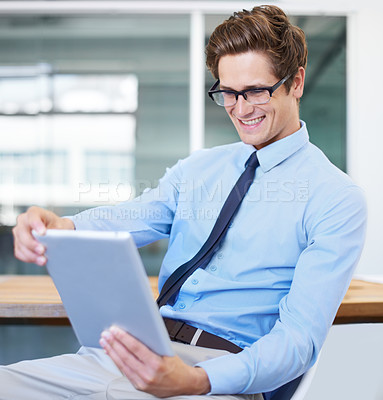 Buy stock photo A handsome young businessman using his digital tablet
