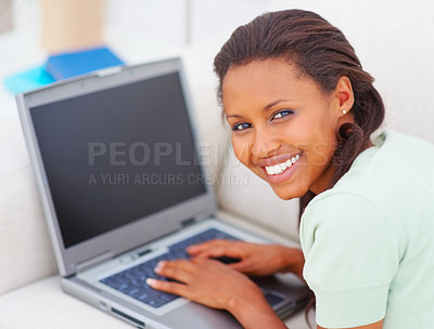 Buy stock photo Closeup portrait of a young African American female lying a couch using a laptop
