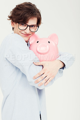 Buy stock photo Portrait of a young man hugging a piggy bank closely to himself