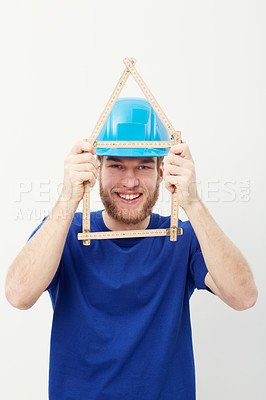 Buy stock photo Portrait of an unshaven young man holding up a carpenter's ruler in the shape of a house