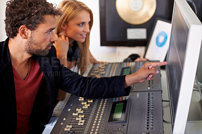Buy stock photo A young audio engineer pointing at a computer screen with his blonde colleague sitting next to him