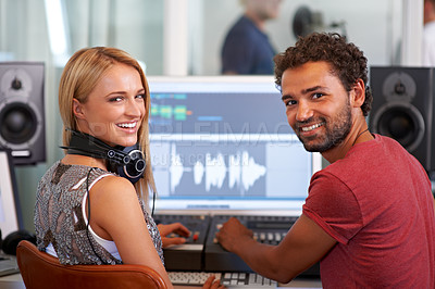 Buy stock photo Two young sound engineers sitting in front of a mixing desk and looking over their shoulders - portrait