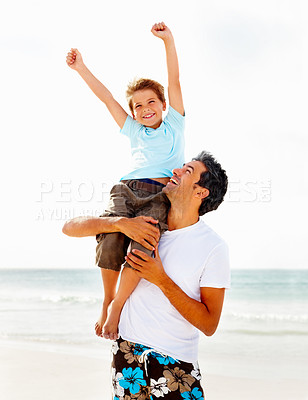 Buy stock photo Adorable young boy sitting on his father's shoulders enjoying at the sea shore