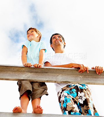Buy stock photo Upward view of a father and son standing on a wooden railing against a clouded sky
