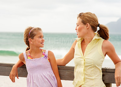 Buy stock photo Mother and daughter having a conversation by a wooden railing at the sea shore