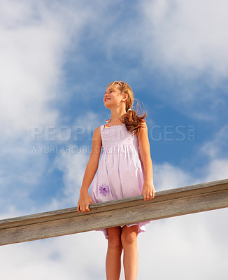Buy stock photo Upward view of a pretty teenage girl standing on a wooden railing against a clouded sky