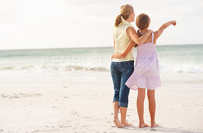 Buy stock photo Rear view of a mother and daughter at the beach, girl pointing towards the sea