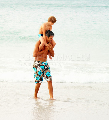 Buy stock photo Happy mature man carrying his son on his shoulders wading at the beach