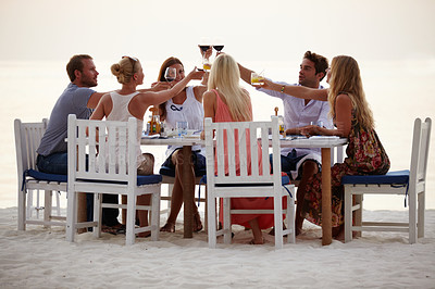Buy stock photo A group of friends toast each other while having dinner on the beach during a summer vacation