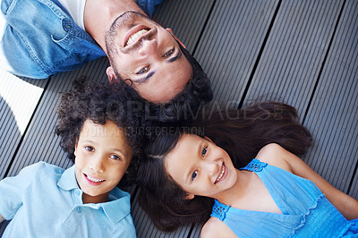 Buy stock photo High angle shot of a family lying on the floor and smiling up at the camera