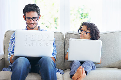 Buy stock photo Shot of a father and sone using laptops on the living room sofa