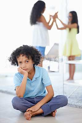 Buy stock photo Portrait of a sad-looking little boy sitting along with his sisters playing in the background