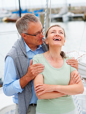 Buy stock photo Happy elderly couple laughing on a joke while on a sailboat