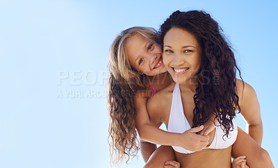 Buy stock photo A young mother carrying her daughter on her back on the beach