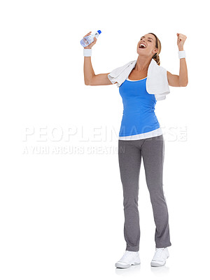 Buy stock photo Healthy young woman holding a bottle of mineral water and feeling triumphant while isolated on white