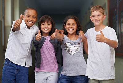 Buy stock photo Four friends standing arm-in-arm and giving you the thumbs-up in the corridor of their school