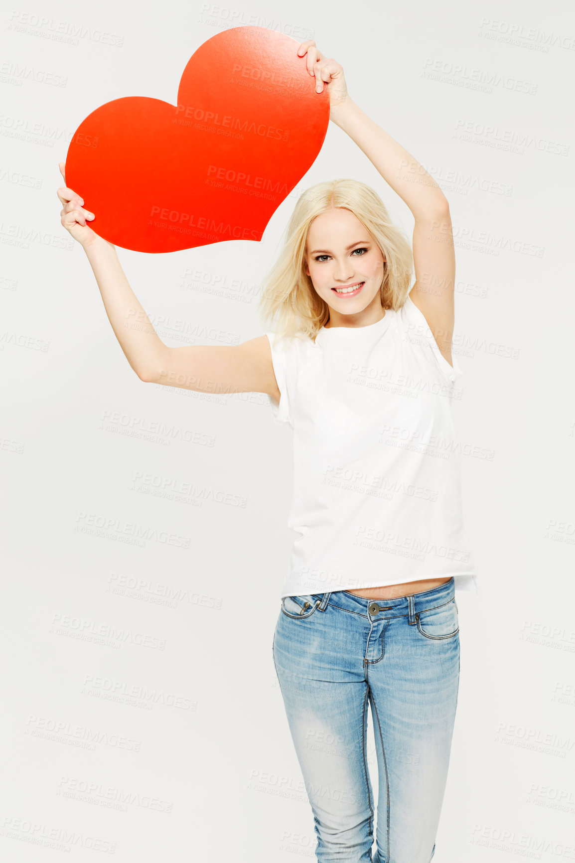 Buy stock photo A beautiful young woman holding a red heart against a white background