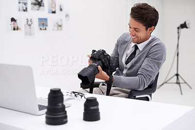 Buy stock photo A photographer sitting at a desk in his office holding a camera