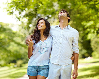 Buy stock photo Cropped shot of an affectionate young couple walking in the park