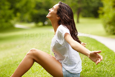 Buy stock photo Cropped shot of a young woman sitting with her arms outstretched in the park