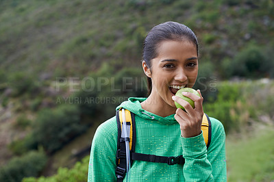 Buy stock photo Cropped view of a young hiker enjoying an apple on the trail