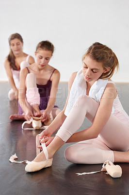 Buy stock photo Young teen ballet dancers fastening their slippers before a class