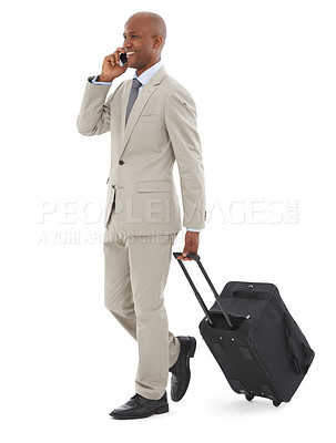 Buy stock photo A young African=American businessman speaking on his phone while walking with luggage