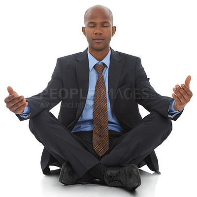 Buy stock photo An African-American businessman sitting meditating against a white background