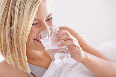 Buy stock photo A young woman drinking a glass of water before bed