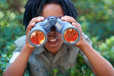Buy stock photo A young boy looking through his binoculars