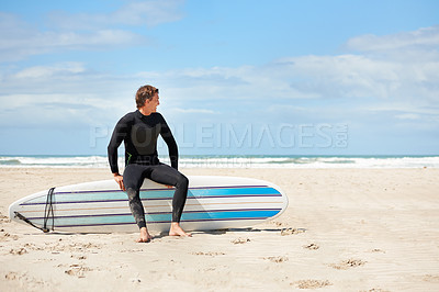 Buy stock photo Full length shot of a young surfer sitting on his board at the beach
